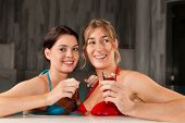 Two female friends drinking tea in swimming pool; they doing wellness in their vacation