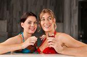 zwei Freundinnen trinken Tee im Schwimmbad; machen sie Wellness in ihrem Urlaub