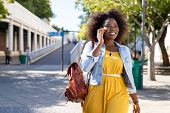 Happy young woman in casual walking while talking over phone. Cheerful african american girl with cu poster