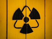 Radioactivity Sign, Close-up. Sign Of Radiation On A Yellow Wooden Board. Radioactive Sign - Symbol  poster