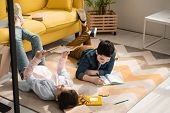 Adorable Kids Lying On Floor At Home And Doing Schoolwork Together poster