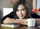 Teenage Or Young Woman At Table With Bible And Coffee Cup