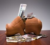 stock photo of piggy_bank  - Broken Piggy Bank with Swedish money in a studio - JPG