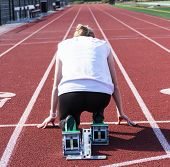 The View From Behind The Starting Blocks Of A High School Female Sprinter Ready To Run Down The Trac poster