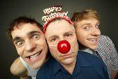 stock photo of prank  - Two guys having fun playing pranks on a senior man celebrating birthday or fool - JPG