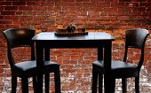 French Bistro - table, chairs with a brick wall background.