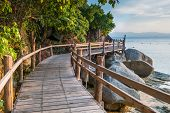 Scenic sea coastline of the Phangan island in Thailand with wooden path along the rocky shore poster
