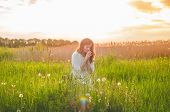 Girl Closed Her Eyes, Praying In A Field During Beautiful Sunset. Hands Folded In Prayer Concept For poster