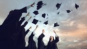 A Group Of Graduates Throws Hats Up Into The Sky. poster