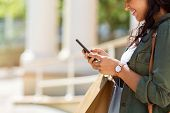 Closeup of woman hands holding shopping bags and using smartphone outdoor. Shopaholic girl checking  poster
