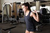 Woman Full Of Determination Doing Behind The Neck Barbell Shoulder Press In Health Club poster