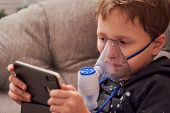 Child Makes Inhalation Nebulizer At Home. On The Face Wearing A Mask Nebulizer Inhaling Vapor Spraye poster