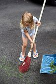 Little Girl Helps Her Parents Collect Grass In The Yard. Seasonal Gardening. Cleaning The Yard poster