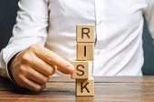 Man Removes Blocks With The Word Risk. The Concept Of Reducing Possible Risks. Insurance, Stability  poster