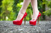 stock photo of stiletto  - Sexy female high heeled red shoes on the way - JPG