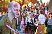 Male Zombie With Stab Wound Walks In Halloween Parade