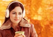 Closeup portrait of young beautiful woman drink coffee in autumnal park, wearing warm earmuff, happy