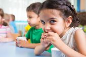 stock photo of daycare  - Cute little children drinking milk at daycare - JPG