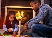 Afro father and little daughter playing together in living room floor by fireplace.