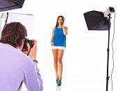 Young model poses for young photographer in photo studio