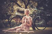 image of natural blonde  - Dreaming blond retro woman with a book sitting on a meadow - JPG