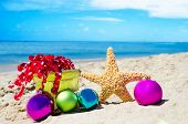 image of starfish  - Starfish with gift box and christmas balls on the beach by the ocean  - JPG