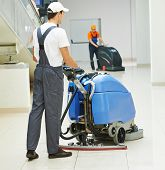 Cleaner male man workers with mop in uniform cleaning corridor pass or hall floor of business buildi
