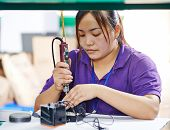 foto of production  - female chinese worker woman assembling production at line conveyor in china factory manufacturing - JPG