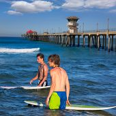 surfers waiting for the waves on Huntington beach pier California [ photo-illustration]