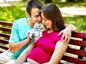Pregnant woman, holding flower with man  outdoor in park.