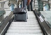 stock photo of escalator  - Businessman with his luggage going up on the escalator - JPG