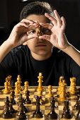 foto of 11 year old  - An 11 year old boy thinking about his next move during a chess game.
