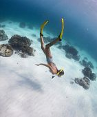 Young lady snorkeling and diving on a breath hold in a clear tropical sea