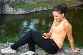 Young woman using smartphone at park with earphones