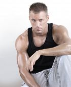 Good looking young muscular masculine man with great arms against neutral background