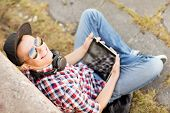 summer holidays, teenage and technology concept - teenager with headphones and tablet pc outside