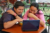 Cute Hispanic Couple With Laptop