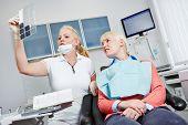 Dentista olhar imagem de raio-x dos dentes de um paciente do sexo feminino