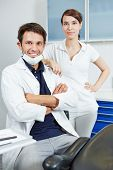 Competent dentist team with dental assistant in dental practice