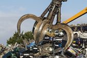 pic of scrap-iron  - Close up of a Crane grab in a Scrapyard swinging above scrap cars - JPG