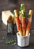 stock photo of smoked ham  - Grissini bread sticks with prosciutto ham arugula and parmesan cheese - JPG