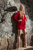 stock photo of mini dress  - Young fashion blonde woman posing in red mini dress in front of stone background - JPG