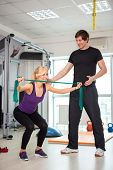 personal trainer man coach and woman exercising with rubber bands