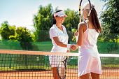 Women handshaking after playing a tennis match