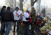 KIEV, UKRAINE - February 21, 2014: Ukrainian revolution, Euromaidan. Medical volunteers helps soldie