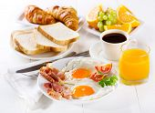 stock photo of croissant  - breakfast with fried eggs croissants juice coffee and fruits - JPG