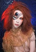 stock photo of woman dragon  - Young  ginger woman in artistic image and with artistic visage - JPG