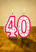 Burning birthday candles number 40 on a wooden background
