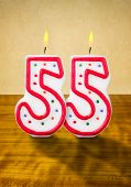 Burning birthday candles number 55 on a wooden background