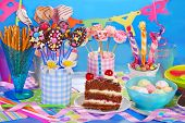 stock photo of tort  - colorful birthday party table with chocolate torte and homemade sweets for kids on blue background - JPG